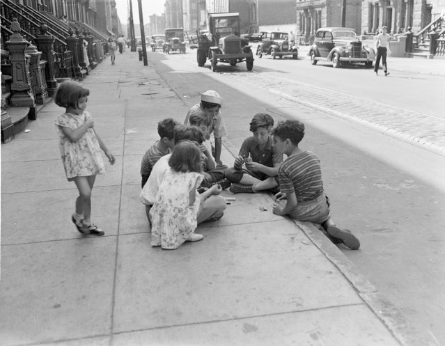 Children play cards while sitting on the curb in a Brooklyn slum in New York, July 19, 1939. (Photo by AP Photo)