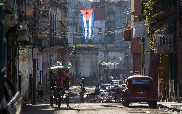 A Cuban flag hangs across a street in Havana, Cuba, Saturday, August 13, 2016. (Photo by Desmond Boylan/AP Photo)