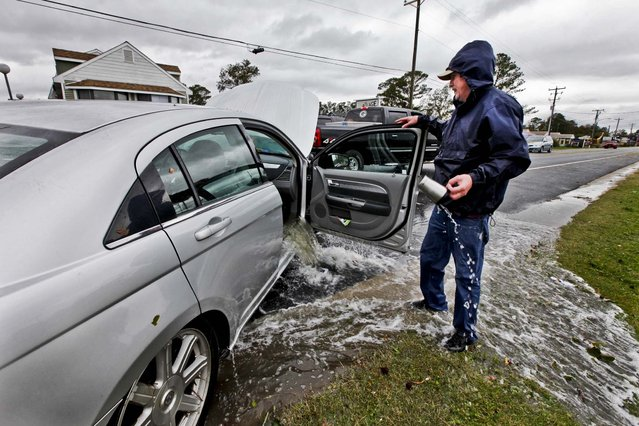 Glenn Heartley watches floodwaters from superstorm Sandy pour out of his car after it was pulled out of a creek in Chincoteague, Va., Tuesday, Oct. 30, 2012.  Heartley and his wife were swept off the road into a shallow creek during Monday's storm. (Photo by Steve Helber/AP Photo)