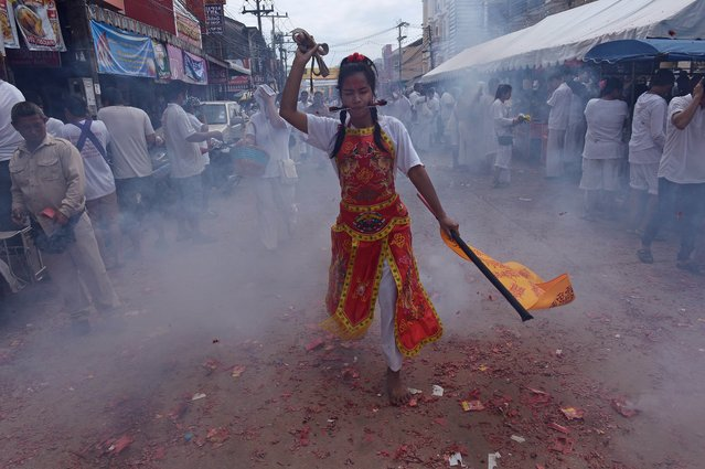 A devotee of the Chinese Jui Tui Shrine with her cheeks pierced by metal rods dances amid exploding fire-crackers during a street procession during the annual Vegetarian Festival in the southern Thai town of Phuket on September 30, 2014. During the festival, which begins on the first evening of the ninth lunar month and lasts nine days, religious devotees slash themselves with swords, pierce their cheeks with sharp objects and commit other painful acts to purify themselves, taking on the sins of the community. (Photo by Christophe Archambault/AFP Photo)
