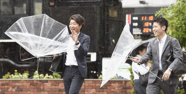 Pedestrians hold broken umbrellas on a street in Tokyo while a powerful typhoon approaches Tokyo, Monday, October 6, 2014. (Photo by AP Photo/Kyodo News)