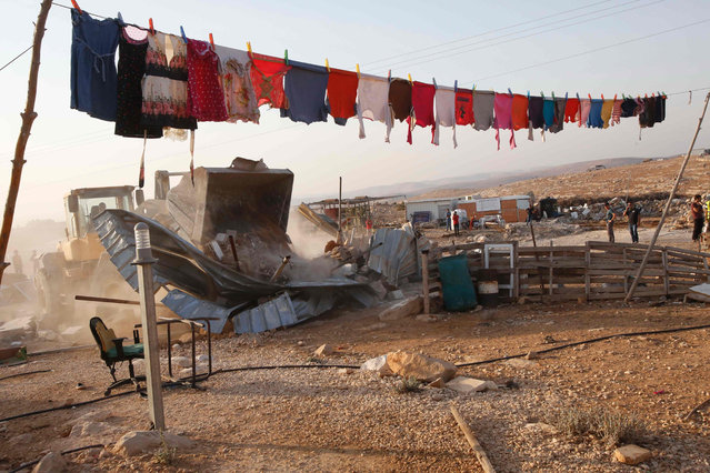A general view shows a washing line above Palestinian a home that was destroyed by Israeli bulldozers in the southern West Bank village of Umm al-Kheir, near the Israeli settlment of Karmel, on August 24, 2016, after Israeli authorities said it was built without permission. (Photo by Hazem Bader/AFP Photo)