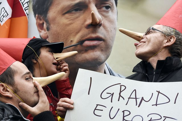 "Members of Italian unions pose in front of a poster of Italian Prime Minister Matteo Renzi with Pinocchio's nose and a placard reading ""The big Europeans gather for jobs"" prior a European Union (EU) extraordinary summit on ""Growth and Employment"" on October 8, 2014 in Milan. Deep divisions within the European Union over the rules governing the euro will be aired once more at an emergency jobs summit today. (Photo by Olivier Morin/AFP Photo)"