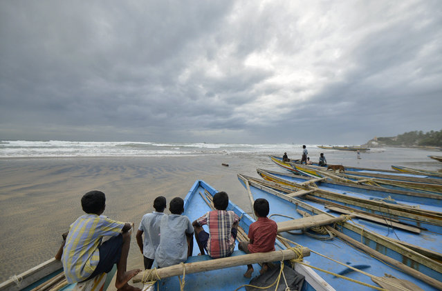 Children sit on fishing boats by the shore before being evacuated, at Visakhapatnam in Andhra Pradesh October 11, 2014. (Photo by R. Narendra/Reuters)