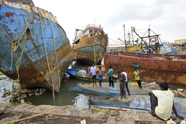 People stand on boats damaged by strong winds caused by Cyclone Hudhud in the southern Indian city of Visakhapatnam October 13, 2014. Cyclone Hudhud powered its way inland over eastern India on Monday, leaving a swathe of destruction but the loss of life appeared limited after tens of thousands of people sought safety in storm shelters, aid workers and officials said. (Photo by R. Narendra/Reuters)