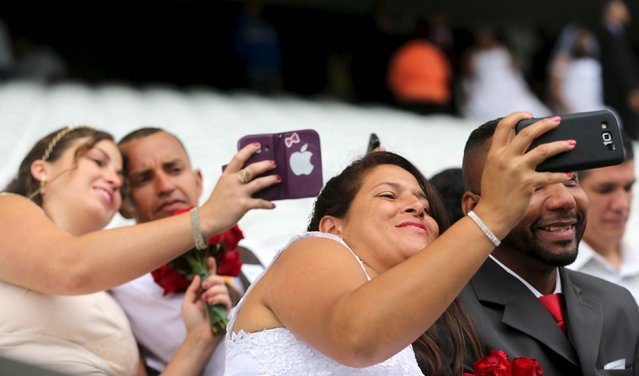 Couples take selfies during a mass wedding ceremony at Arena Corinthians soccer stadium in Sao Paulo, Brazil, September 26, 2015. (Photo by Paulo Whitaker/Reuters)