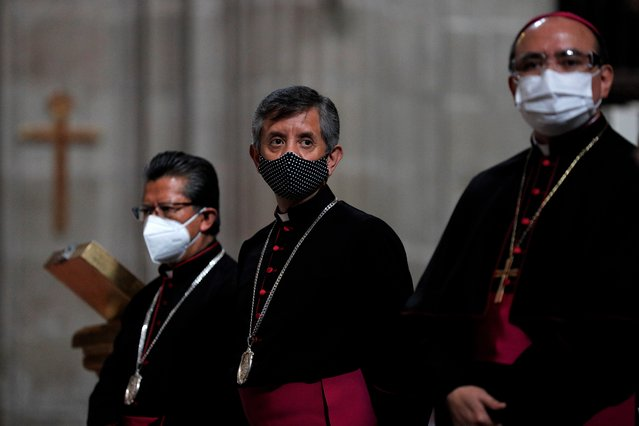 Catholic priests stand inside the Metropolitan Cathedral ahead of the first Mass open to the public amidst the ongoing coronavirus pandemic, in Mexico City, Sunday, July 26, 2020. (Photo by Rebecca Blackwell/AP Photo)