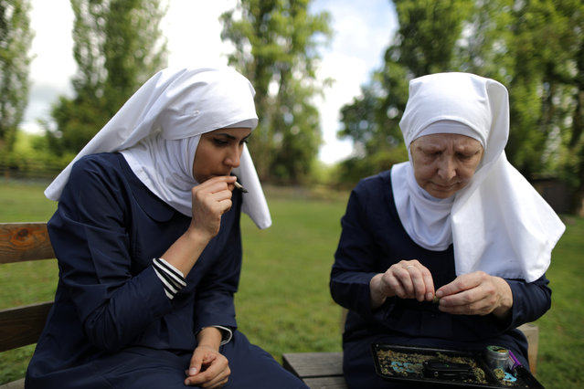 "California ""weed nun"" Christine Meeusen, 57, (R), and India Delgado, who goes by the name Sister Eevee, smoke a joint at Sisters of the Valley near Merced, California, April 18, 2017. (Photo by Lucy Nicholson/Reuters)"