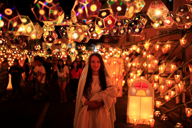 A girl dressed as the Virgin Mary poses for a photo during the Lantern Festival celebrating the eve of the nativity of the Virgin Mary in Ahuchapan, El Salvador September 7, 2016. (Photo by Jose Cabezas/Reuters)