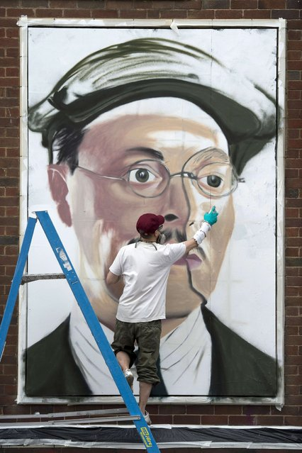 "French street artist ""Akse"" creates an artwork as he takes part in the ""Sand Sea & Spray"" Urban Art Festival in Blackpool, north west England on July 11, 2015. (Photo by Oli Scarff/AFP Photo)"