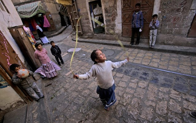 Yemeni girl Zamzam Mansour, 10, center, skips with a rope while playing with other children next to her father's shop in an alley of the old city of  Sanaa, Yemen, Saturday, November 27, 2010. (Photo by Muhammed Muheisen/AP Photo)