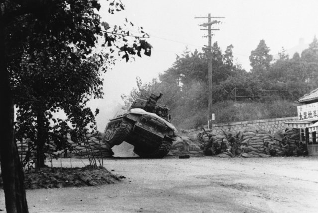 An American tank crashes roughshod through an enemy roadblock near Seoul, South Korea, October 7, 1950, as 7th Division infantrymen prepare to exploit the breakthrough and put an end to Red Sniper fire in this sector of the Korean front. (Photo by AP Photo)