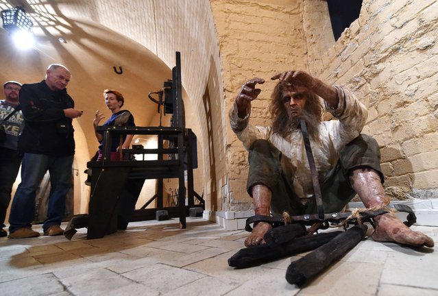 """Visitors view an installation at the exhibition """"Torture and Execution in the Middle Ages"""" during its opening in Kiev on October 7, 2015. (Photo by Sergei Supinsky/AFP Photo)"""
