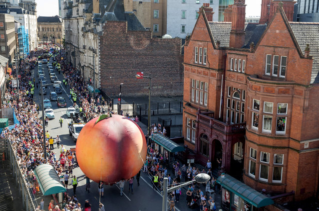 Members of the public gather to watch a giant peach as it is moved through the centre of Cardiff as part of a street performance to mark the start of City of the Unexpected, a celebration of the author Roald Dahl, on September 17, 2016 in Cardiff, Wales. The celebrated author was born in Cardiff 100 years ago this month and to celebrate the Welsh capital is hosting a series of events this weekend. (Photo by Matt Cardy/Getty Images)