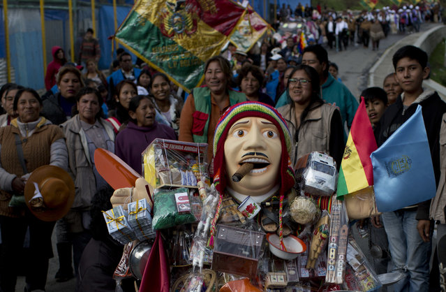 People accompany the statue of Ekeko, the Bolivian god of prosperity and the central figure of the Alasita miniature fair, in La Paz, Bolivia, Tuesday, January 23, 2018. (Photo by Juan Karita/AP Photo)