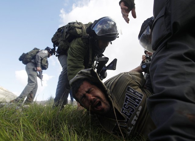 Israeli border police detain a Palestinian man after a group of activists set up tents and makeshift structures in protest against a nearby Jewish settlement in the West Bank village of Burin, south of Nablus February 2, 2013. Palestinians who set up a makeshift encampment in the occupied West Bank on Saturday clashed with Israeli soldiers and settlers and some light injuries were sustained. (Photo by Mohamad Torokman/Reuters)