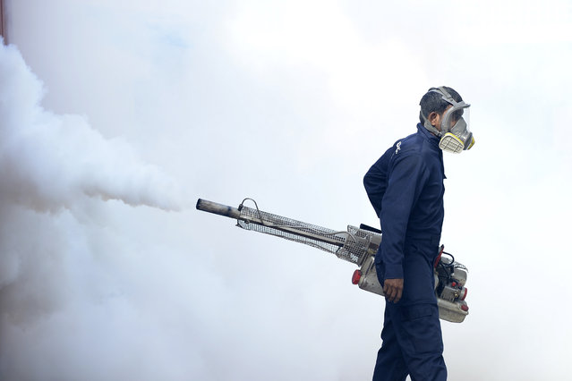 A municipal worker fumigates an area to kill off mosquitos inside the Lumbini school in Colombo on September 15, 2020. (Photo by Lakruwan Wanniarachchi/AFP Photo)