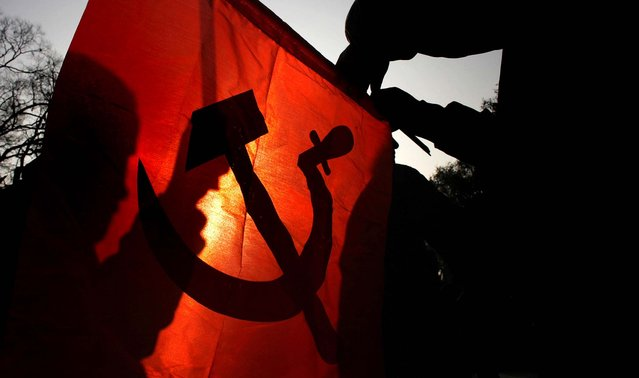 A member of the splinter faction of the Unified Communist Party of Nepal Maoist carries a communist flag during a general strike in Katmandu called by the party against the decision to form an interim government led by the Supreme Court chief justice, on February 19, 2013. Nepal's major political parties agreed to form an interim government and hold elections in June, likely ending a deadlock that has left the nation without a fully functioning government since last year. (Photo by Niranjan Shrestha/Associated Press)