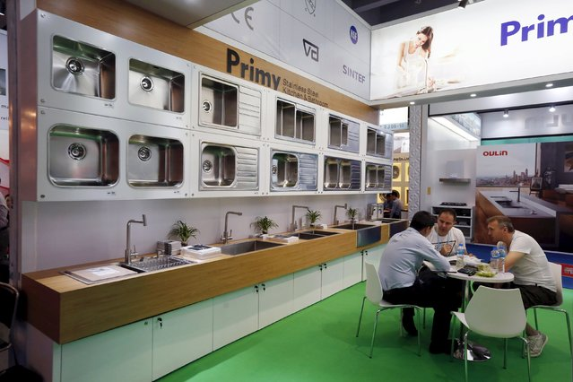 Foreign buyers have a discussion with an exhibitor at a booth selling kitchen and bathroom products during the China Import and Export Fair, also known as Canton Fair, in the southern Chinese city of Guangzhou October 15, 2015. (Photo by Bobby Yip/Reuters)