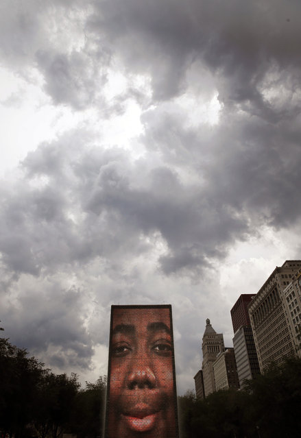 Storm clouds roll above the Crown Fountain in Chicago's Millennium Park bringing temporary relief to the Midwest's excessive heat Thursday, July 21, 2016, in Chicago. The fountain is an interactive work of public art and video sculpture. (Photo by Charles Rex Arbogast/AP Photo)