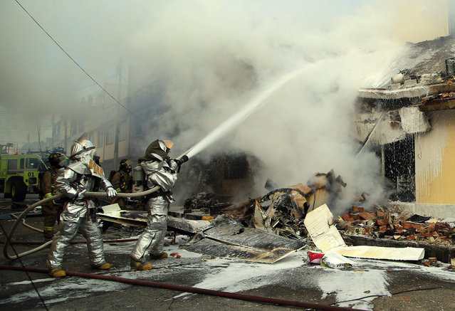 Firefighters put out a fire after a twin-engine plane crashed in a residential area, in Bogota, Colombia, 18 October 2015. Five people died and seven were injured in the crash in the urban area west of Bogota, according to sources of the Institute of Risk Management and Climate (Idiger). The aircraft crashed around 16:20 local time (21:20 GMT), in the locality of Engativa, near the El Dorado International Airport, from where it took off minutes earlier, the Civil Aeronautics (Aerocivil) said. (Photo by Mauricio Osorio/EPA)