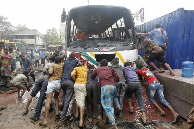 People help a driver to move his bus after activists of the Bangladesh Nationalist Party (BNP) set fire to it during a nationwide strike in Dhaka March 12, 2013. Police on Monday arrested more than 200 opposition leaders, including BNP acting secretary general Mirza Fakhrul Islam Alamgir following a violent clash in front of their party office. The BNP announced a nationwide dawn-to-dusk shutdown on Tuesday, claiming that Monday's raid on the BNP office was an attack on the opposition 18-party rally, local media reported. (Photo by Andrew Biraj/Reuters)