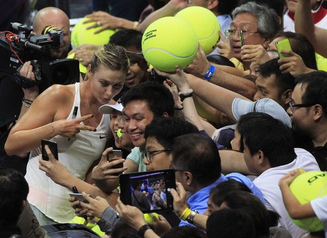Maria Sharapova of the Manila Mavericks team gestures while posing for photos with fans after beating Kristina Mladenovic of the UAE Royals team in their women's singles tennis match at the International Premier Tennis League (IPTL) competition in Manila November 28, 2014. (Photo by Romeo Ranoco/Reuters)