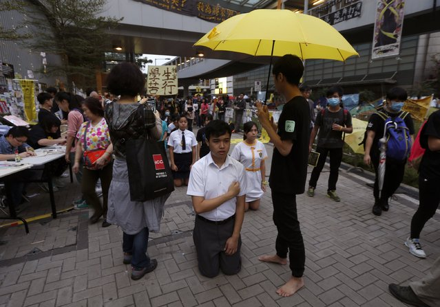 """A leader carries a yellow umbrella, symbol of the Occupy Central civil disobedience movement, as other secondary school students perform a barefoot """"pilgrimage of suffering"""" to support the movement at the Admiralty protest site in Hong Kong November 30, 2014. (Photo by Bobby Yip/Reuters)"""