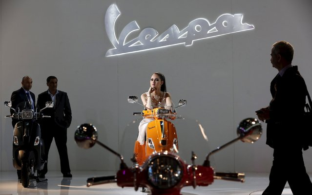 A model poses with a Vespa 946 scooter as visitors walk around during the Indian Auto Expo in Greater Noida, on the outskirts of New Delhi, India in this February 6, 2014 file photo. Piaggio, owner of the Vespa scooter brand, is expected to report Q3 results this week. (Photo by Adnan Abidi/Reuters)