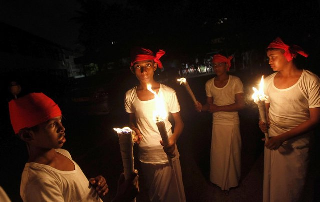 Sri Lankan youths hold up torches to mark Earth Hour in Colombo March 23, 2013. EarthHour, when everyone around the world is asked to turn off lights for an hour from 8.30 p.m. local time, is meant as a show of support for tougher action to confront climate change. (Photo by Dinuka Liyanawatte/Reuters)