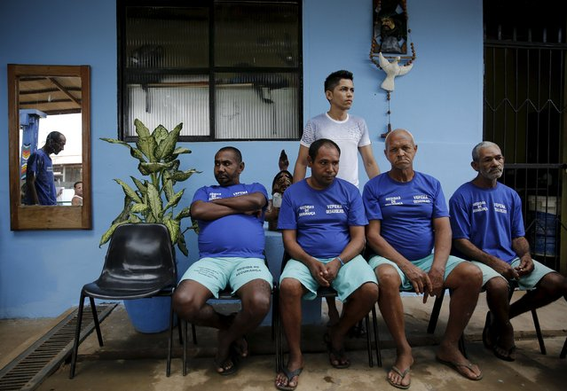 Inmates (wearing blue L-R) Messias Manoel, Jose Nunes, Manoel Joaquim and Rivaldavio da Silva, who are patients at a psychiatric prison, sit as a fellow prisoner Tiago (back), 24, takes care of them as part of the ACUDA programme, at a complex of ten prisons in Porto Velho, Rondonia State, Brazil, August 28, 2015. (Photo by Nacho Doce/Reuters)