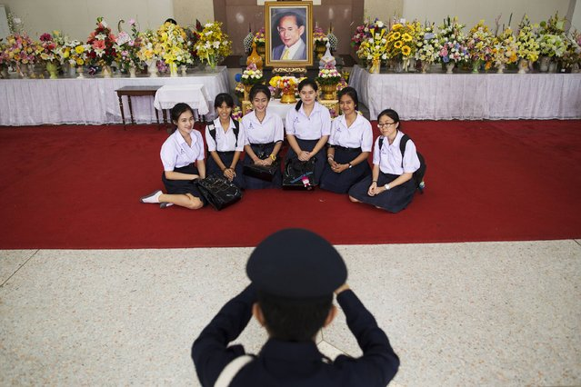 Schoolgirls have their picture taken after praying for the health of Thailand's King Bhumibol Adulyadej at the Siriraj hospital where he is staying, in Bangkok December 4, 2014. The revered King, the world's longest reigning monarch, will turn 87 years old on December 5. (Photo by Damir Sagolj/Reuters)