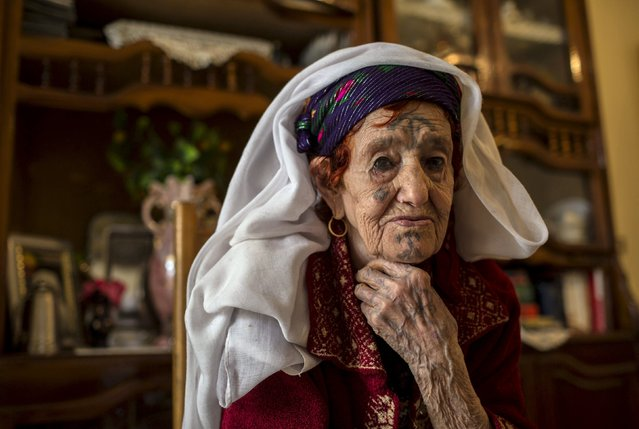 """Fatma Badredine, 94, a berber woman from the Chaouia region, who has facial tattoos, sits inside her house in Arris at the Aures Mountain near the eastern city of Batna, Algeria October 8, 2015. Traditionally, the more a woman was tattooed the higher she was prized by local men. Badredine was tattooed aged 13 years old by a nomadic woman from the Sahara region. """"I had to endure excruciating pain just to look pretty"""", Badredine said. (Photo by Zohra Bensemra/Reuters)"""
