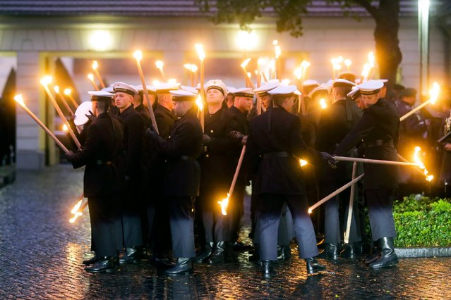 Honor guards light their torches prior to an official dinner held by German President Joachim Gauck and his partner Daniela Schadt for Sweden's King Carl XVI Gustaf and Queen Silvia at the Bellevue Palace in Berlin, October 5, 2016. (Photo by Markus Schreiber/AP Photo)