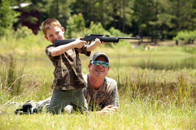 Jeremy Chavez helps his son Ryan, 6, with target practice before a wild hog hunt at Great Southern Outdoors Wildlife Plantation in Union Springs, Alabama, Saturday June 16, 2012. Fast, smart and dangerous, the wild boar was once the most prized hunter's catch in ancient Greece. Now it is becoming a popular target of hunters in the United States. An explosion of wild pig populations has become such a nuisance that hunting seasons are being flung wide open for wild hog across the nation. Picture taken June 16, 2012. (Photo by Michael Spooneybarger/Reuters)