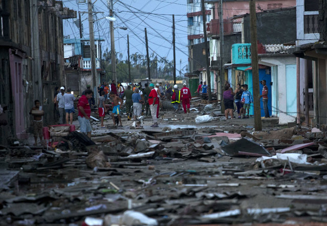 Red Cross workers and residents walk among the damage caused by Hurricane Matthew in Baracoa, Cuba, Wednesday, October 5, 2016. The hurricane rolled across the sparsely populated tip of Cuba overnight, destroying dozens of homes in Cuba's easternmost city, Baracoa, and leaving hundreds of others damaged. (Photo by Ramon Espinosa/AP Photo)
