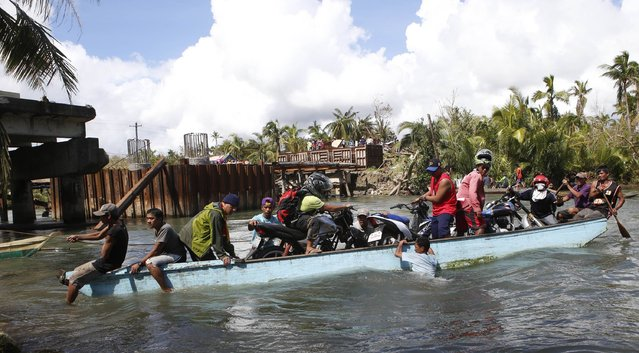 Typhoon Hagupit victims and their motorcycles are transported on a boat next to a damaged bridge in San Julian, Eastern Samar in central Philippines December 10, 2014. (Photo by Erik De Castro/Reuters)