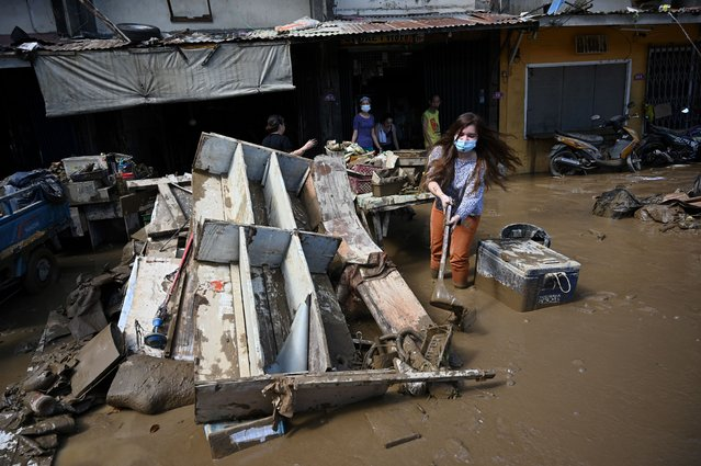 A resident uses a dust pan to shovel away muddy water next to debris in front of her flood-damaged home in a residential area in Marikina City, suburban Manila, on November 13, 2020, a day after Typhoon Vamco hit the capital area bringing heavy rains and floodings. (Photo by Ted Aljibe/AFP Photo)