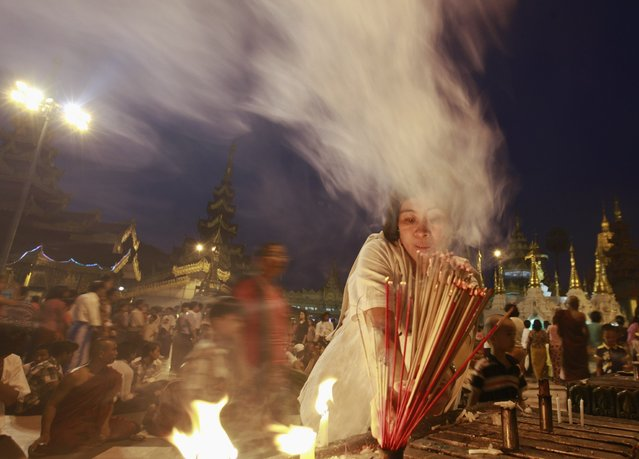A woman lights frankincense as she prays at Shwedagon pagoda on the first day of Myanmar's traditional New Year in Yangon April 17, 2013. (Photo by Soe Zeya Tun/Reuters)