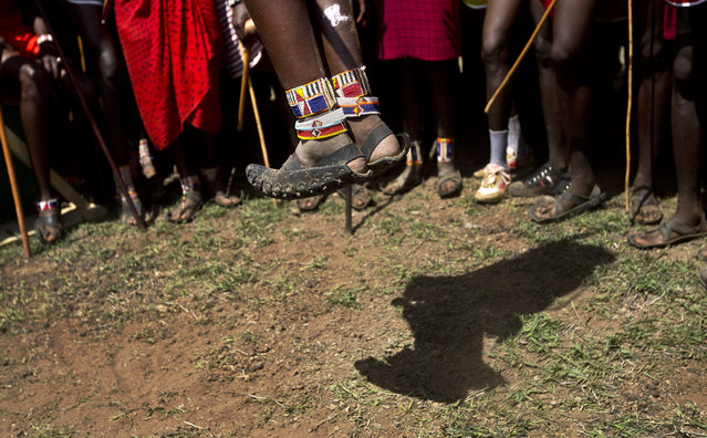 A Maasai warrior makes the high jump, in which athletes must touch a high line with the top of their heads, at the annual Maasai Olympics in the Sidai Oleng Wildlife Sanctuary near Mt. Kilimanjaro, in southern Kenya, Saturday, December 13, 2014. (Photo by Ben Curtis/AP Photo)