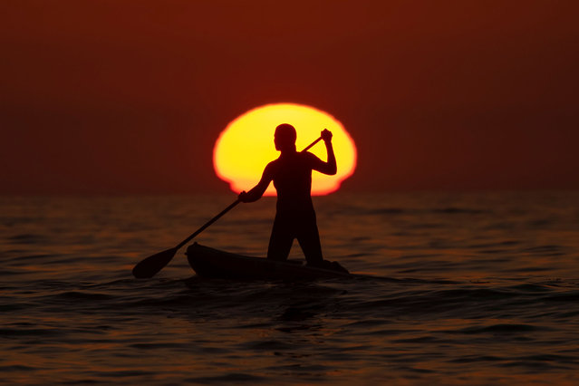 A paddle boarder paddles in towards shore as the sun sets at Cardiff State Beach in Cardiff, California, U.S., November 1, 2020. (Photo by Mike Blake/Reuters)