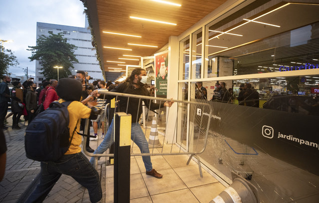 Demonstrators use a crowd control barrier to smash into the entrance of a Carrefour supermarket during a protest against the murder of Black man Joao Alberto Silveira Freitas at a different Carrefour supermarket the night before, on Brazil's National Black Consciousness Day in Rio de Janeiro, Brazil, Friday, November 20, 2020. Freitas died after being beaten by supermarket security guards in the southern Brazilian city of Porto Alegre, sparking outrage as videos of the incident circulated on social media. (Photo by Andre Penner/AP Photo)