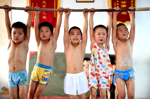 These images of young children training were taken at a gymnastics summer camp in Bozhou, Anhui province, China on July 28, 2015. Children with promise are selected to attend, and their families hope training will not only benefit their children physically but also increase 'willpower', according to China News Service. (Photo by ChinaFotoPress/ChinaFotoPress via Getty Images)