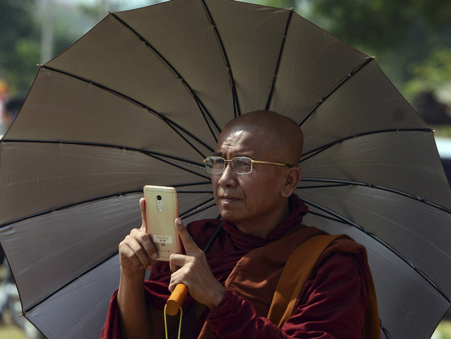 A member of a Myanmar's ultra-nationalist Buddhist group takes photos with his mobile phone during a protest rally in Nayptitaw, Myanmar, Saturday, May 20, 2017, against Religious Minister Thura Aung Ko for his intervention in a case in which Myanmar Now news chief reporter Swe Win leveled allegations against Wirathu, a high-profile leader of the Myanmar Buddhist organization known as Ma Ba Tha, after the monk praised the assassination in January of prominent Muslim lawyer Ko Ni who was a legal advisor to Aung San Suu Kyi's government. Tensions between Buddhist and Muslims has spread across Myanmar since violent conflict broke out between ethnic Rakhine Buddhists and Muslim Rohingya in 2012. (Photo by Aung Shine Oo/AP Photo)