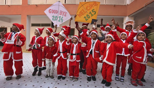 Indian students dressed as Santa Claus hold kites and dance as they participate in a function to welcome the New Year at a school in Ahmadabad, India, Wednesday, December 31, 2014. (Photo by Ajit Solanki/AP Photo)