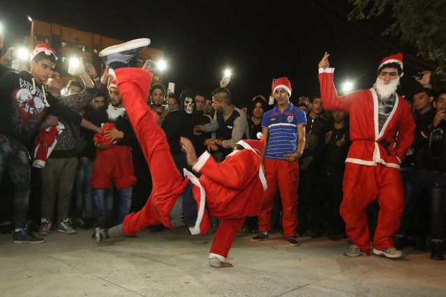Acrobatic performers, dressed in Santa Claus costumes,   celebrate the New Year at Firdous Square in Baghdad, Iraq, Wednesday, December 31, 2014. (Photo by Hadi Mizban/AP Photo)