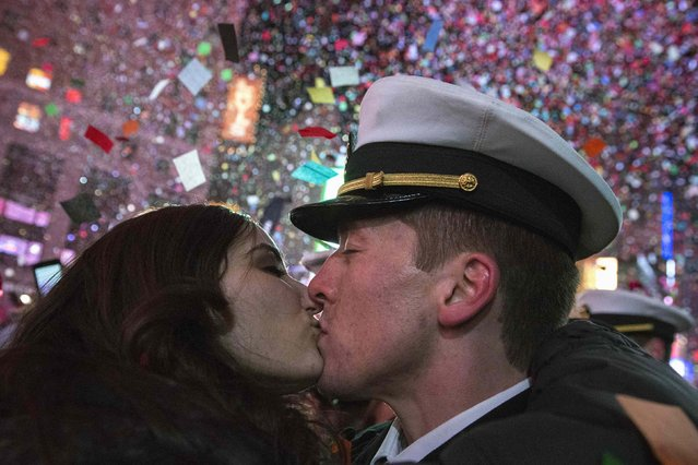 A couple kisses amid confetti as the clock strikes midnight during New Year's Eve celebrations in Times Square, New York January 1, 2015. (Photo by Stephanie Keith/Reuters)