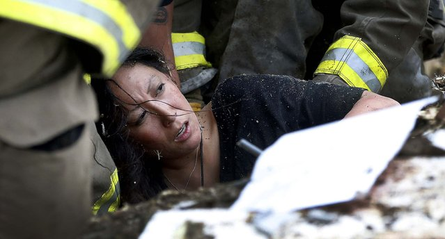 A woman is pulled out from under debris at the Plaza Towers School in Moore. (Photo by Sue Ogrocki/Associated Press)