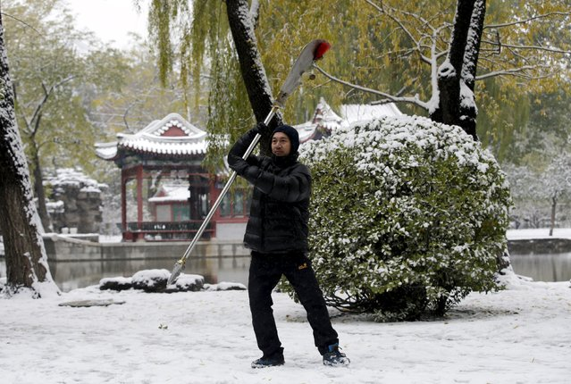 A resident wields a Chinese Wushu blade as part of morning exercises, during snowfall at a park in central Beijing, China, November 22, 2015. (Photo by Jason Lee/Reuters)
