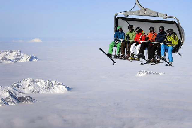 Skiers are seen on a cable car above the fog on December 1, 2012 in the Titlis mountain above Engelberg, Central Switzerland. (Photo by Fabrice Coffrini/AFP Photo)